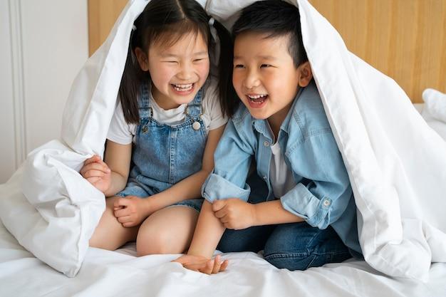 Filhos completos sentados sob um cobertor