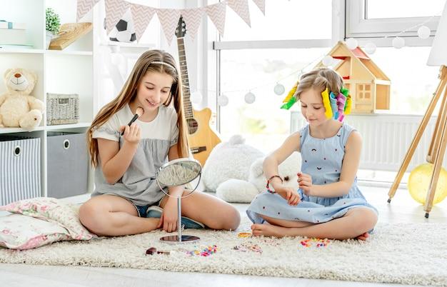 Filhos de meninas fazendo maquiagem com pincel