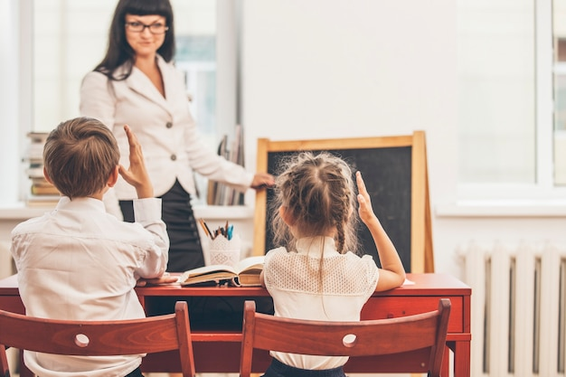 Filhos de meninos e meninas com o professor na escola