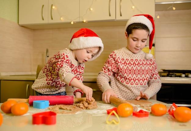 Filhos de papai noel fazendo biscoitos para o papai noel na cozinha aconchegante. chefs de papai noel. biscoitos natalinos. crianças engraçadas preparam comida de férias para a família.