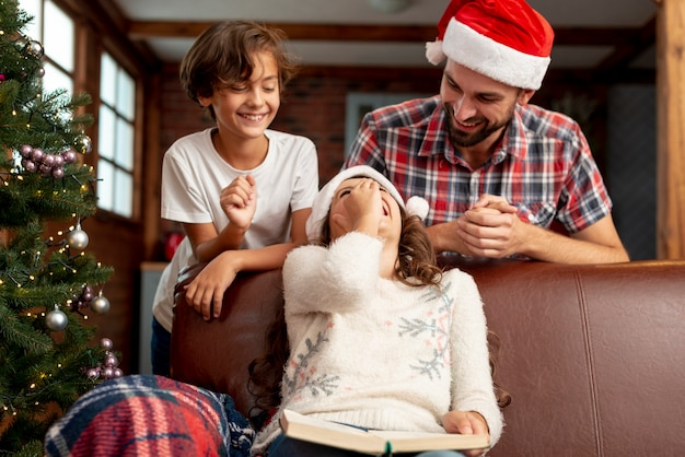 Filhos de tiro médio com pai rindo juntos