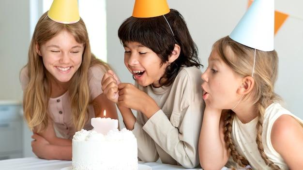 Filhos de tiro médio comemorando com bolo