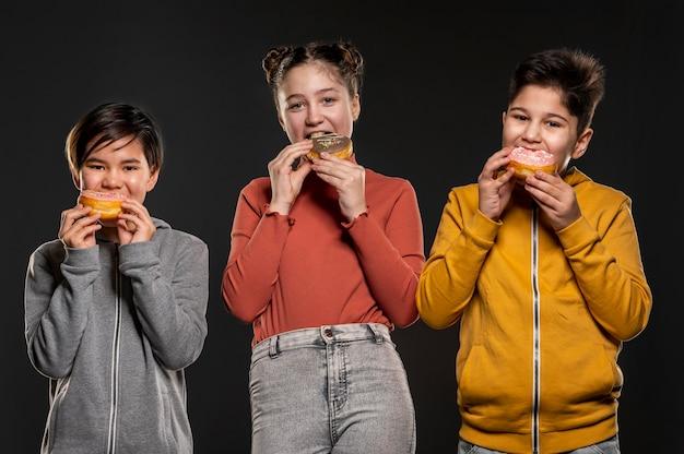 Filhos de tiro médio comendo donuts