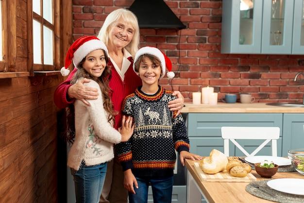 Filhos de tiro médio e avó posando na cozinha