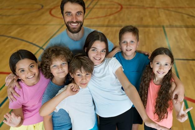 Filhos de tiro médio e professora posando