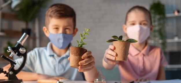 Filhos de tiro médio segurando vasos de plantas