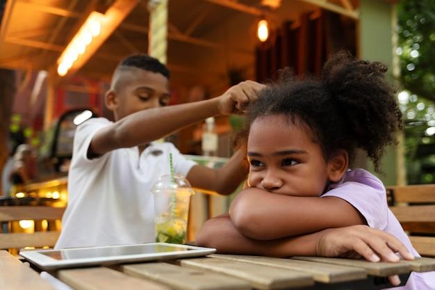 Filhos de tiro médio sentados à mesa com o dispositivo