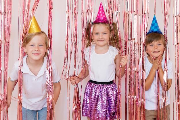 Filhos de tiro médio usando chapéus de festa