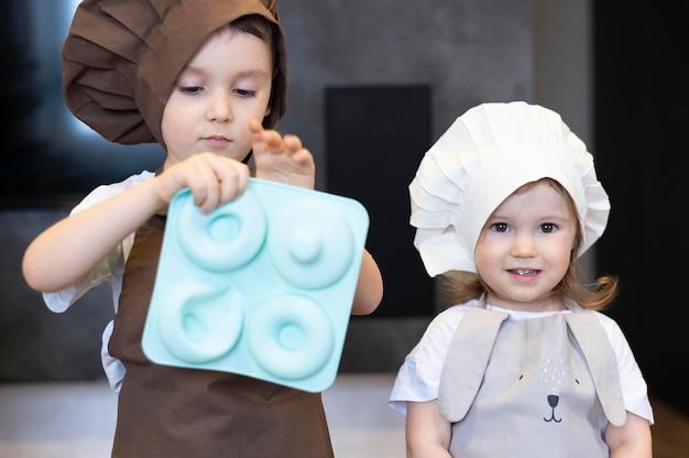 Filhos de tiro médio usando roupas de cozinheira