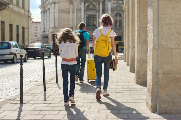 Filhos duas filhas de meninas e pai, turistas andando pela cidade com mochilas e uma mala. viagem, família, férias, turismo, conceito de verão