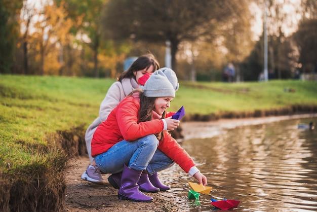 Filhos e mãe brincando com barquinhos de papel no lago