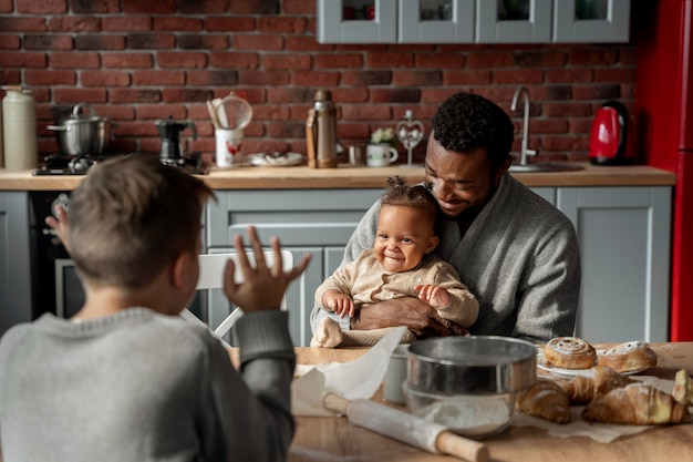 Filhos e pai na mesa, tiro médio