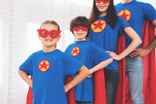 Filhos e pais em trajes de super-heróis.