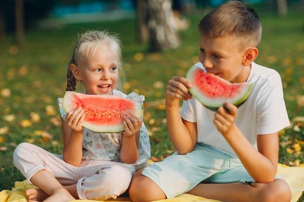 Filhos fofos comendo melancia suculenta no parque de outono