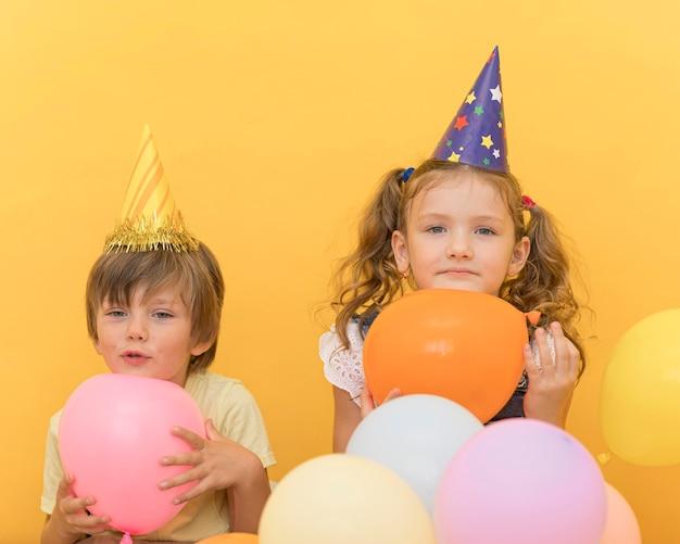Filhos fofos de tiro médio segurando balões