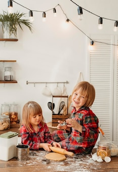 Filhos fofos fazendo biscoitos de natal juntos na cozinha