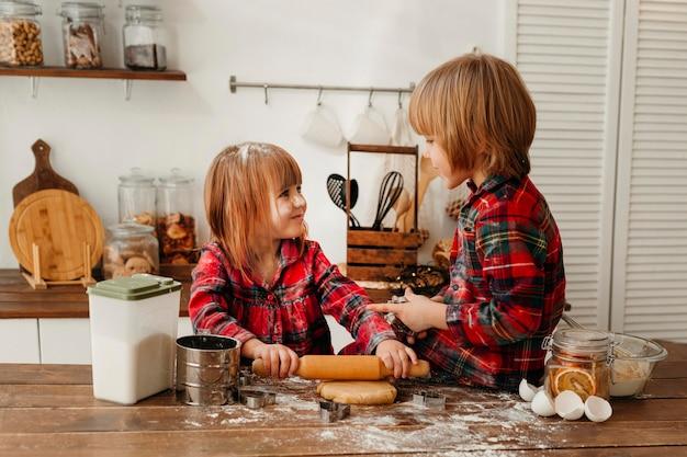 Filhos fofos fazendo biscoitos de natal juntos