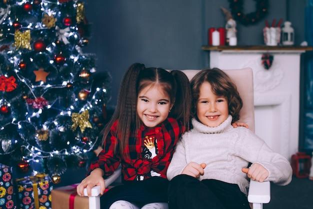 Filhos irmão e irmã estão sentados em uma cadeira perto da árvore do ano novo, olhando para o quadro e sorrindo.