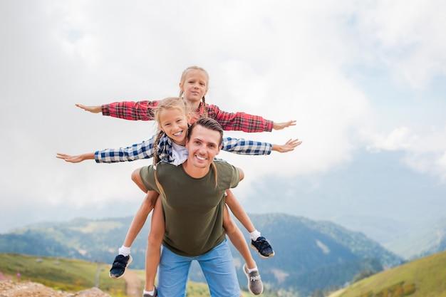 Filhos lindos e homem feliz nas montanhas ao fundo do nevoeiro