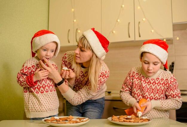 Filhos rindo e mãe fofa decorando biscoitos de natal de gengibre