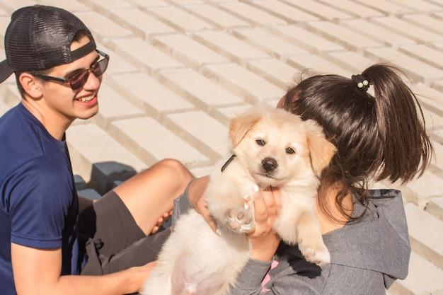 Filhote de cachorro feliz sendo levantado por um casal de fitness.