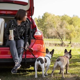 Filhotes de cachorro fofos e mulher sentada no carro