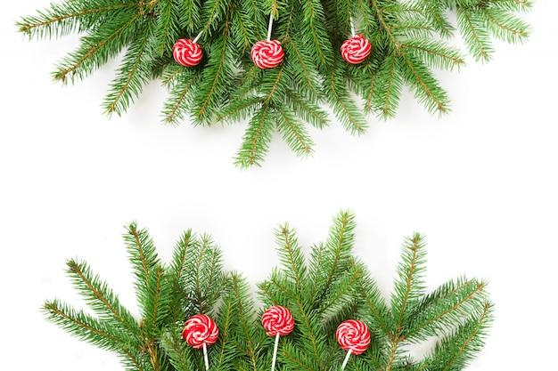 Filiais de árvore do natal e lolipop vermelho no fundo branco.