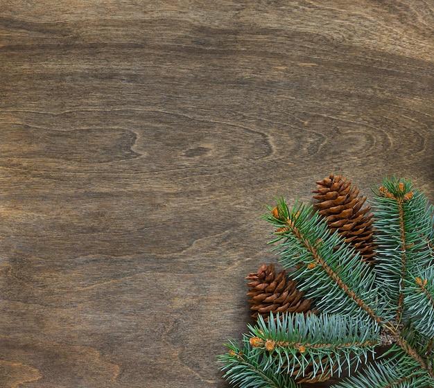 Filial de abeto de natal em fundo de madeira com cones.