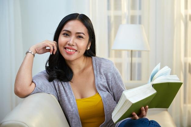 Filipino feminino com livro, olhando para a câmera