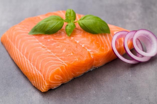 Fille de salmão fresco com especiarias no fundo cinza.