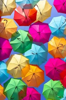 Filmado de baixo, uma bela exibição de guarda-chuvas pendurados coloridos