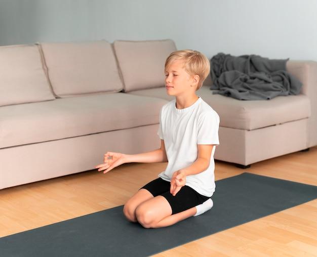Filmagem completa da criança meditando dentro de casa