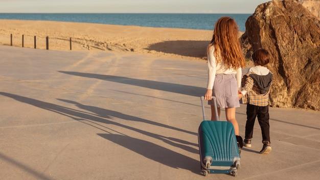 Filmagem completa de crianças carregando bagagem