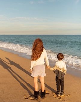 Filmagem completa de crianças de mãos dadas na praia