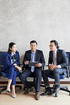 Filmagem completa de três empresários sentados próximos um do outro