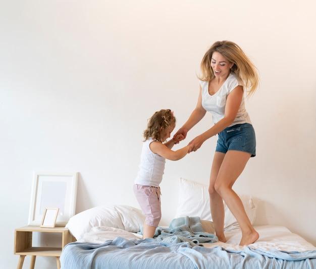 Filmagem completa mãe e filha dançando na cama