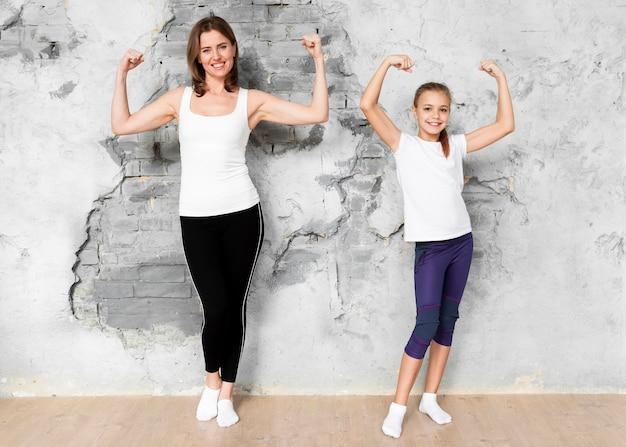 Filmagem completa mãe e filha, flexionando os músculos do braço