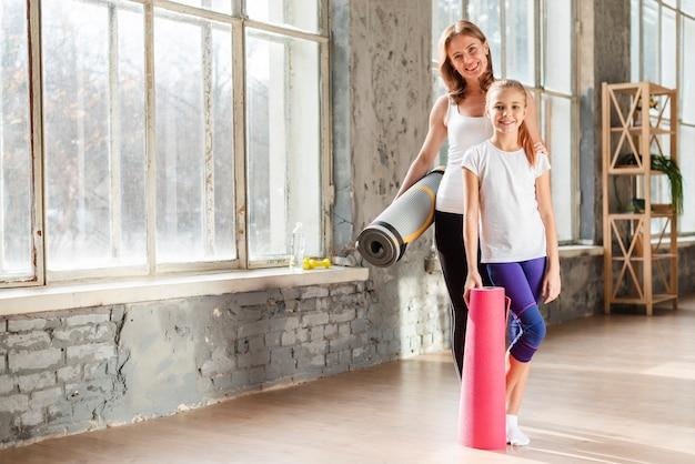 Filmagem completa mãe e filha segurando tapetes de ioga