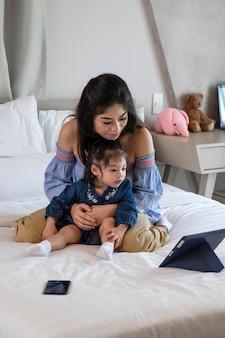 Filmagem completa, mãe e menina olhando para o tablet