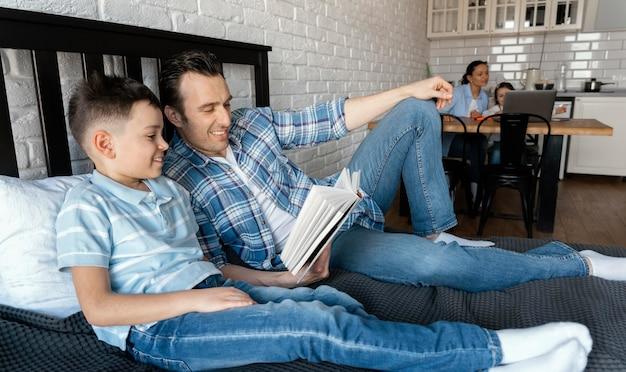 Filmagem completa, pai e filho lendo na cama