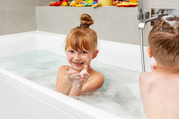 Filmagem média, crianças sentadas na banheira