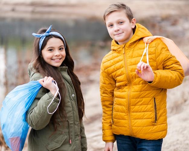 Filmagem média de crianças segurando um saco de plástico