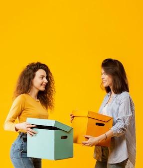 Filmagem média de mulheres carregando caixas