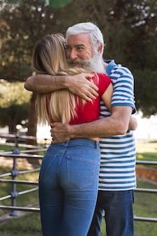 Filmagem média de pai e filha abraçando