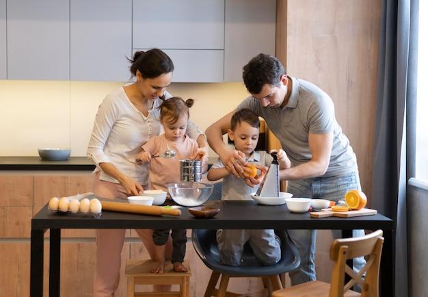 Filmagem média em família cozinhando em casa