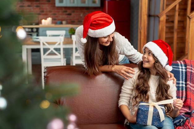Filmagem média feliz filha e mãe com presente