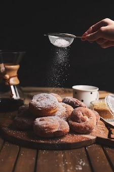 Filmagem vertical de deliciosos donuts cobra polvilhados com açúcar de confeiteiro e café químico