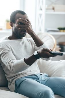 Filme assustador. africano jovem e bonito segurando um controle remoto enquanto está sentado no sofá em casa