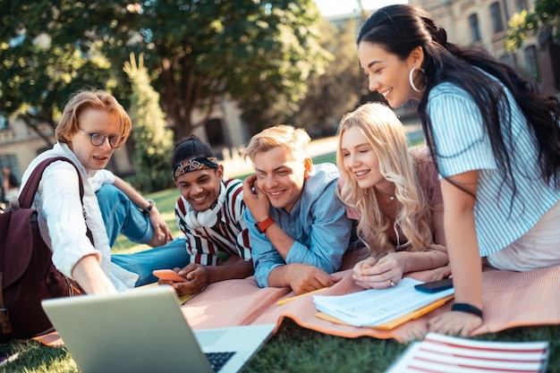 Filme com amigos. alunos alegres assistindo a um filme em um laptop deitado sobre um cobertor no pátio da universidade juntos.