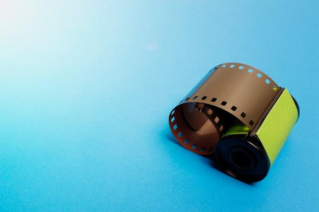 Filme de 35mm, rolo de filme da câmera no fundo azul.